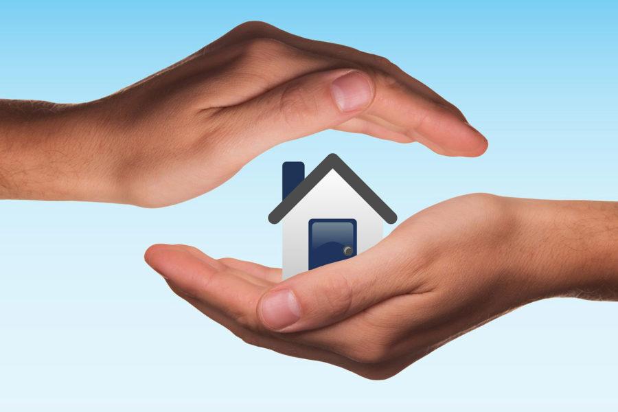 Zwei Hände schützen ein Haus